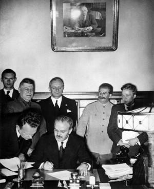 Podpis německo-sovětské smlouvy o neútočení v Moskvě v noci z 23. na 24. srpna 1939. Sedící uprostřed Vjačeslav Molotov, stojící nad ním Joachim von Ribbentrop, stojící vpravo od něj ve světlém saku Josef Stalin. (Foto: NARA)