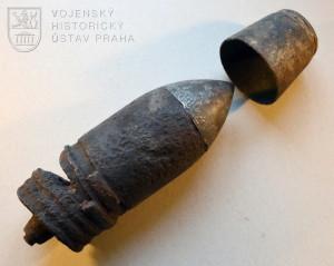 Granát po delaboraci, představná čepice byla k ocelovému jádru přiletovaná cínem. Korozí narušený povrch dokládá méně kvalitní ocel z konce války.