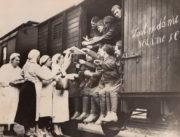 Prostý a současně vše říkající vlastenecký nápis je hotov. Skupina žen, patrně dobrovolných sester Československého červeného kříže, nabízí mobilizovaným mužům horký nápoj a svačinu před cestou na místo určení. Odhodlání občanů k obraně bylo v těchto chvílích nesmírné. FOTO: archiv Karel Straka