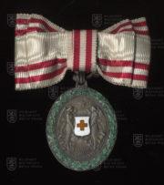 Čestné vyznamenání za zásluhy o Červený kříž, stříbrná medaile na dámské stuze s válečnou dekorací (avers). FOTO VHÚ.