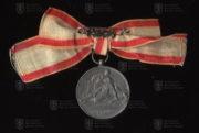 Srbská medaile Za službu srbskému červenému kříži na dámské stuze, 1. stupeň - verze z období balkánských válek 1912-1913 (revers). FOTO VHÚ.